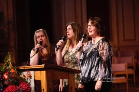 Polly Moody, Julie Wernham, and Debbie Stanton singing.
